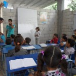 Volunteers with the Syrian Arab Red Crescent, distribute UNICEF-provided school supplies to conflict-affected children attending a remedial education class in Talbiseh. ©SARC/2013