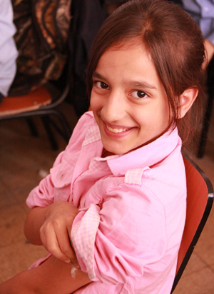 A girl student is all smiles after she received an MMR vaccination at a Damascus school. ©UNICEF/Syria-2013/Rashidi