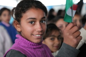 A girl waves a Kurdish flag at a ceremony to welcome the Japanese Ambassador to Iraq Mr Masato Takaoka to Darashakran refugee camp in northern Iraq. The ambassador made the visit to view the programmes that the people of Japan are funding and which UNICEF and its partners are implementing.  . ©UNICEF/Iraq-2013/Niles