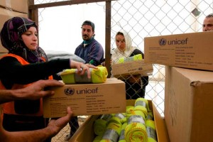 Refugees pick up UNICEF clothes kits and IKEA blankets at the Zaatari distribution. entre. ©UNICEF/Jordan-2013/Noorani