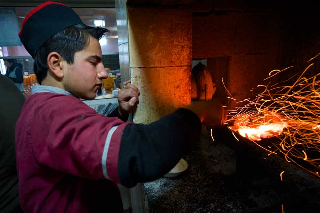 Ahmed helps out in the kitchen by cooking kebabs for customers. ©UNICEF/Iraq-2013/Noorani