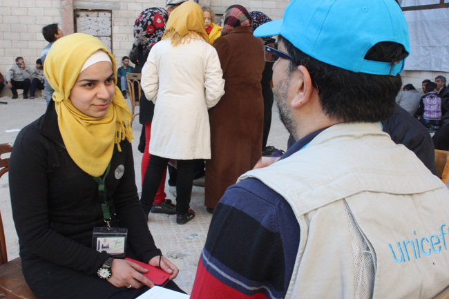 Haya, 21, volunteers at a centre in Homs where men who were recently evacuated from the Old City are being interviewed. She helps out by playing with their children and preparing meals. ©UNICEF/ Syria-2014/Rashidi