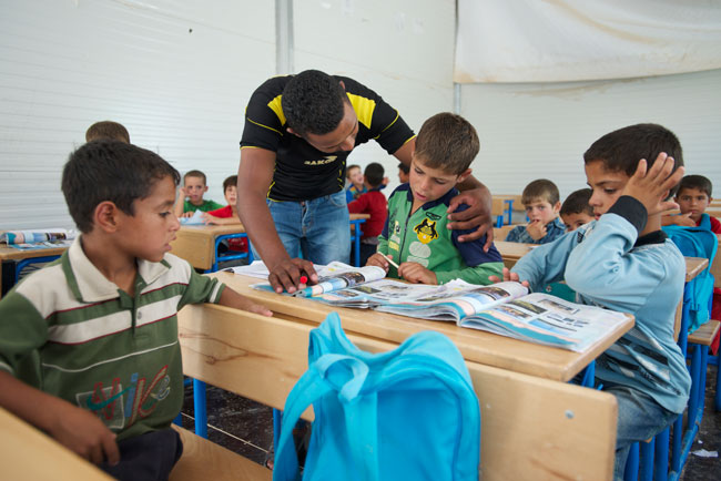 Teacher helps a boy during a Grade 1 science class in a UNICEF-supported school in Za'atari camp for Syrian refugees in Jordan. © UNICEF/NYHQ2013-0562/Noorani