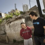 12-year-old Esmaeil laughs with Orlando Bloom near the shelter he shares with his parents and five siblings. The family have exhausted their savings, and none of the children of school-age is in school.