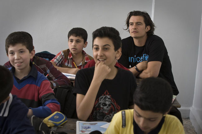 UNICEF Goodwill Ambassador Orlando Bloom (background, right) joins students during a Grade 6 English class, at Omar Bin Abdul Aziz Boys School in the northern city of Irbid in Jordan. © UNICEF/NYHQ2014-0437/Diffidenti
