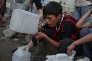 boy drinks the last drops of water in his jerry can while he queues with other children. ©UNICEF/Syria-2014/Khabieh
