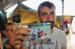 Mohammad shows a picture of family members working on the farm in happier times. Following a fatal shelling attack, surviving family members fled to Tartous where they live in a shelter with others displaced by the conflict. ©UNICEF/Syria-2014/Tiku